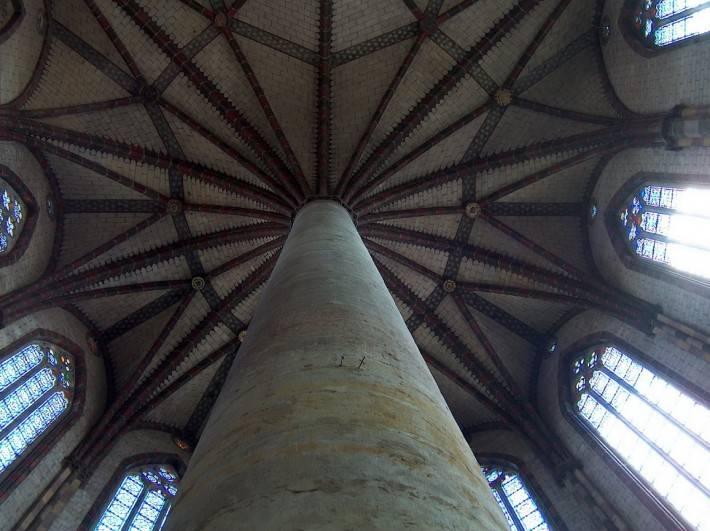 Каменная колонна в центре зала упирается в кирпичный потолок