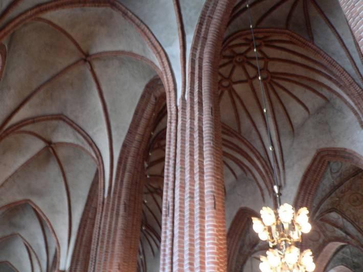 Сводчатый белый потолок с колоннами из красного кирпича