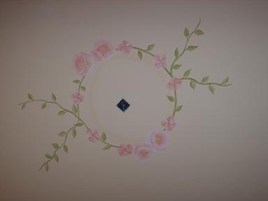 Нарисованная розетка в виде розы и стеблей на потолке