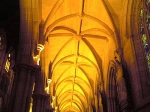 Ряд арок с колонами упирающимися в каменный сводчатый потолок